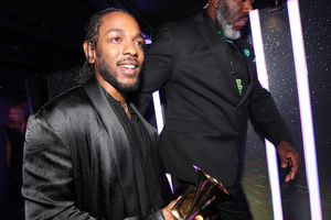 Black man with black beard and cornrows in black coat and shirt holds gold statue while walking beside Black man in black suit with blue embroidery in front of black background with pink lights