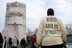 Black demonstrator in yellow shirt with black text and black pants and blue hat walks in front of grey stone monument of Black man and Black people in multicolored clothing in front of blue and grey sky