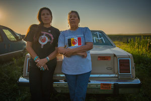 Indigenous woman in black t-shirt with with red text and white and red logos and black pants stands next to Indigenous woman in grey t shirt with red and black and white logo and blue pants in front of beige car and green field and orange and blue sky