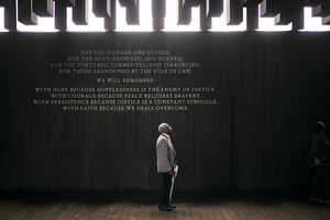 Black man in grey blazer and black pants and shoes stands in front of charcoal wall with grey text underneath brown blocks in front of grey sky