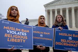 Brown women in gold hijabs and black and blue clothing hold blue signs with white and gold text in front of grey stone building and grey sky