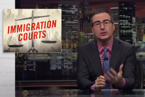 "John Oliver. White man sits at desk in dark suit with blue tie and red and blue checked shirt. Graphic beside him reads, ""Immigration Courts."""
