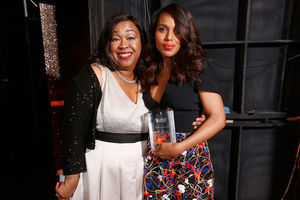 Black woman in black sweater and white dress stands next to Black woman in black blouse and black and red and white skirt holding clear glass award in front of black and brown walls