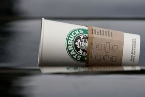 A white Starbucks cup tipped over on its side with a wet cardboard sleeve around it