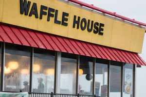 Yellow and black Waffle House sign above red awning and windows.
