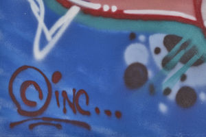Graffiti art with black paint signature on blue and grey background