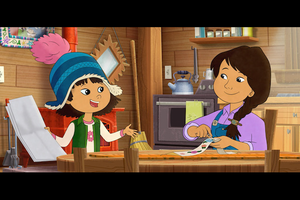 Indigenous girl in blue and pink hat and green vest and white and pink shirt next to Indigenous girl in purple shirt and blue overalls at brown table in front of brown and red and grey house and appliances