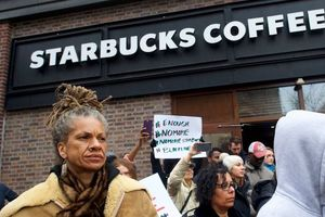 Black woman with dredlocks in front of a Starbucks.
