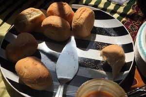 Brown pieces of bread next to silver knife on black and white plate and near glass container with brown sauce