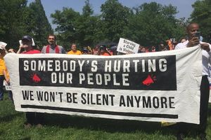 """People outside, standing in grass, holding white, black and red sign that reads, """"Somebody's hurting our people, we won't be silent anymore."""""""