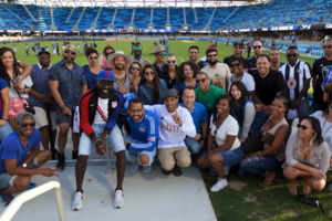 Black women and men in white and blue and brown and black clothing in front of blue stadium seats and green field