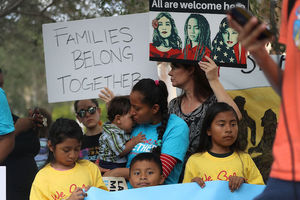 """Brown protesters—including several children—hold signs and banners, including one that says """"Families belong together."""""""
