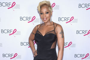 Black woman with blonde hair and black tattoos in black dress in front of white wall with black text and red logos