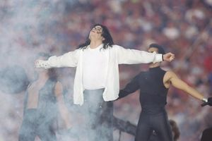 Michael Jackson in white shirt and tshirt and black pants in front of back-up dancers in black outfits and football stadium audience
