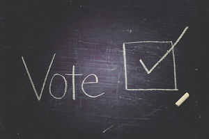 "Blackboard with ""vote"" written in white chalk"