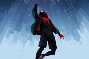 Teenage boy in black and red costume and green hoodie underneath city skyline with grey buildings and navy sky