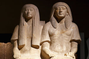 Brown statue depicting two women in front of black background
