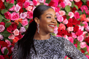 Black woman with black hair in pink lipstick and grey and blue dress smiles in front of wall with pink and red flowers and green leaves