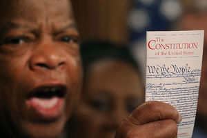"John Lewis. Black man holds small booklet with ""The Constitution of the United States"" on the front."