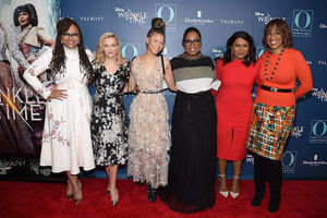 "Ava DuVernay in white dress and cast of ""A Wrinkle in Time"" in multicolored dresses and Gayle King in orange sweater and brown patterned skirt on red carpet in front of navy wall"