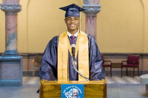 Jaisaan Lovett. Young Black boy smiles while standing behind podium wearing navy graduation cap and gown with yellow sash