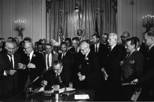 Black-and-white image of Black and White men in suits surrounding White man sitting at a desk