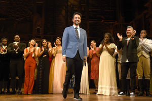 "Cast of ""Hamilton"" in multicolored costumes stands and applauds behind Lin-Manuel Miranda in blue blazer and grey tie and black pants on brown stage"