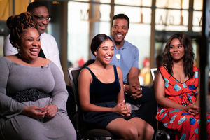 "Angie Thomas in grey dress smiles in front of George Tillman Jr. in white shirt next to ""The Hate U Give"" cast in multicolored clothing, seated three to a row in two rows in front of grey background"