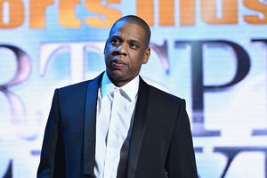Jay-Z in black suit with white shirt in front of blue LED screen with black and orange text