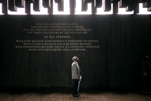 A Black man stands looking up at wooden beams suspended from the ceiling