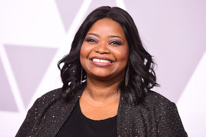 Octavia Spencer smiles in black blouse and sweater with gold glitter in front of white wall with purple triangles and light purple shading