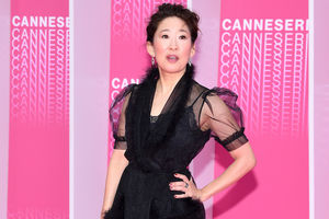 Sandra Oh with black hair in black dress in front of pink wall with pink text