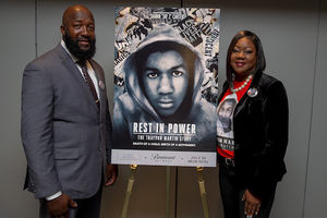 Black man in grey suit and Black woman in black suit with red shirt stand next to black-and-white movie poster with Black child in white hoodie in front of grey wall