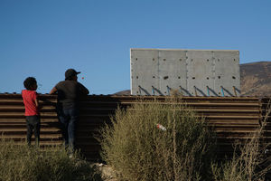 Two people outside standing against a brown steel wall overlooking the construction of a concrete wall