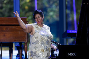 Aretha Franklin in brown dress holds hand out while seated at black piano in front of blue and green background