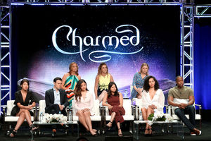 "Cast and creators of ""Charmed"" sit on two-tiered black stage in multicolored clothing in front of purple background"