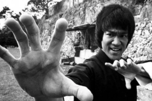 Black-and-white photograph of Bruce Lee with black hair in black shirt in front of stone wall and grass and trees