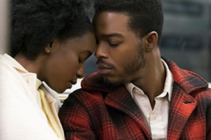 KiKi Layne in yellow shirt next to Stephan James in black and red plaid jacket and white shirt in front of grey background