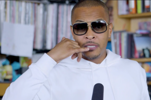 T.I. holds finger to ear in White sweatshirt behind black microphone in front of brown bookshelf with multicolored records