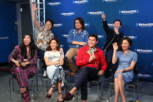 """Crazy Rich Asians"" cast and author in multicolored clothing on black chairs and stools on grey floor and in front of blue wall with white text"