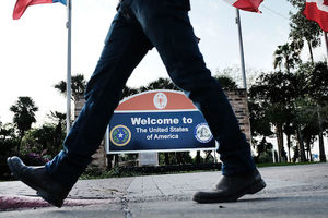 two legs walking at forefront in between them is a sign that says welcome to the united states of america