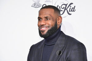 LeBron James smiles in Black suit and turtle neck in front of white wall with black text