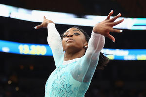 Simone Biles poses in teal gymnastics outfit in front of white lights and darkly lit audience
