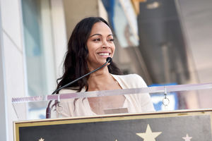 Zoe Saldana in beige dress and blouse behind glass podium with black microphone in front of brown building