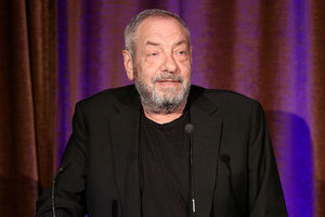Dick Wolf with grey hair and beard in black shirt and blazer in front of brown and purple curtain