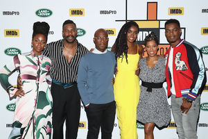 Teyonah Parris, Colman Domingo, Barry Jenkins, KiKi Layne, Regina King and Stephan James stand in multicolored clothing in front of white wall with yellow and black and green logos