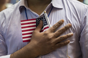 Person holds mini flag to their chest, wearing blue and white striped shirt
