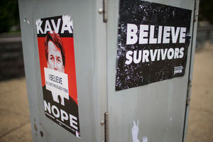 "Red, white and black sign reads ""Kava Nope"" and ""I believe Dr. Christine Blasey Ford."" Black and white sign reads ""Believe Survivors."" Signs pasted to gray electrical box."