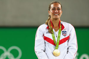 Monica Puig. Brown woman with blonde hair in white warm-up outfit with red accents wears gold medal on green lanyard in front of green and brown wall