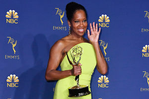 Regina King in lime green dress holding gold award statue in front of blue background with gold text